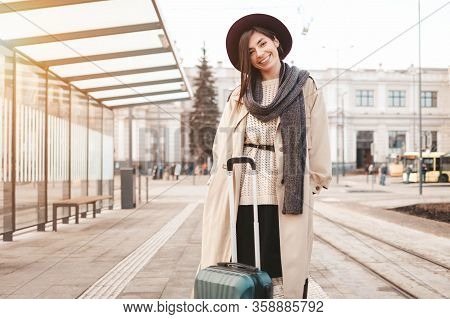 Stylish Girl With A Suitcase Stands At A City Stop Awaiting A Tram