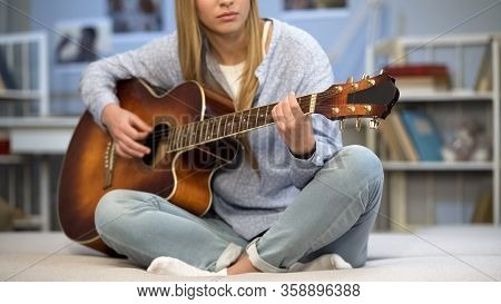 Female Musician Tuning The Guitar On Home Sofa, Enjoying Melody, Practicing