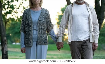 Pensive Aged Couple Holding Hands And Walking Forward, Insecurity About Future