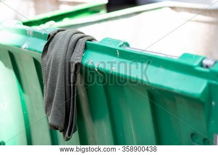 Old Sweater In A Green City Street Garbage Dumpster
