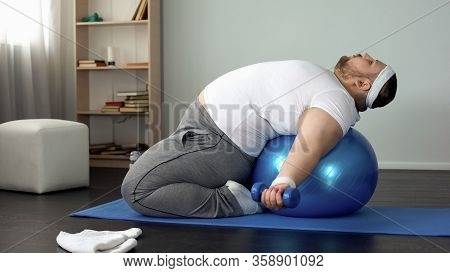 Purposeful Overweight Male Lifting Dumbbells Lying On Fitness Ball, Muscles Pump