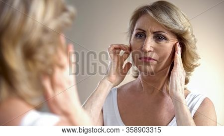 Senior Woman Touching Wrinkled Face, Thinking About Botox Injections, Age