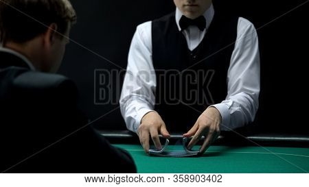 Professional Croupier Shuffling Cards On Green Table For Businessman, Poker Game
