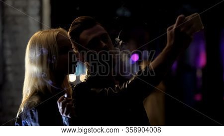 Young Couple Smoking And Taking Selfie In Dark Alley, Nightclub On Background