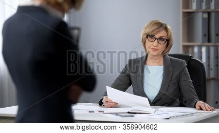 Strict Serious Lady Boss Looking Contemptuously At Secretary, Poor Performance