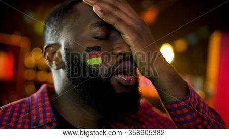 Disappointed German Football Fan With Flag On Cheek Making Facepalm, Team Losing