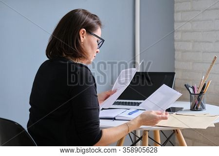 Serious Mature Woman Holding Business Papers In Hands Documents Received In Envelopes By Mail, On De