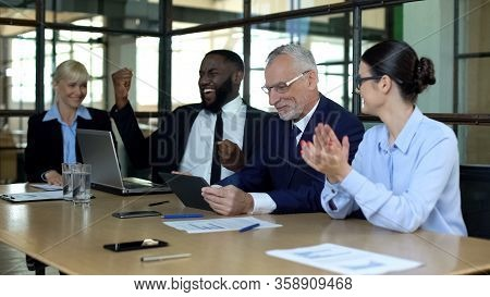 Multiracial Company Employees Celebrating Good News In Office, Successful Deal