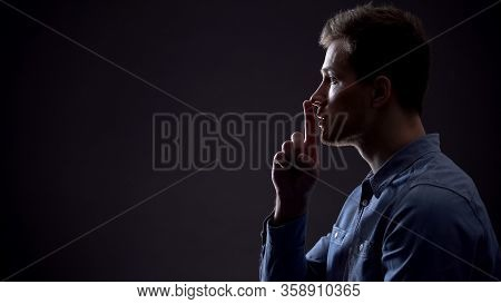 Handsome Young Man Showing Silence Gesture, Mysterious Secret, Side View