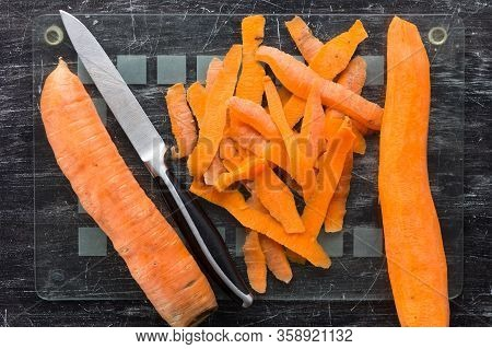 Top View Of Unpeeled Carrot And Peeled Carrot With Peeling And Knife On Glass Cutting Board On The B