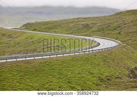 Twisty Scenic Road With Green Landscape In Faroe Islands. Drive