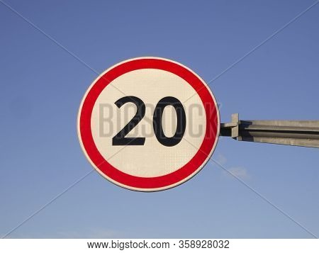Round Road Sign Of Maximum Speed Limit 20 Km / H On Blue Sky Background.