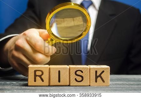 Businessman Holds A Magnifying Glass Over The Word Risk. Financial And Commercial Risk Concept. Risk
