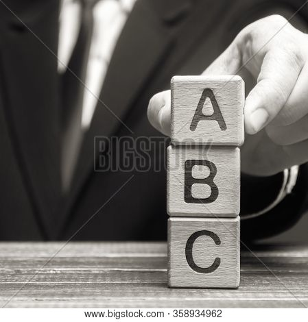 Businessman Puts Wooden Blocks A, B, C. Task List. Alternate Items And Conditions For Implementation