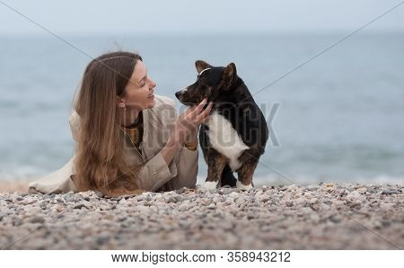 Owner Of A Beautiful Girl With Her Dog Welsh Corgi Cardigan Sitting On The Beach By The Sea. Copyspa