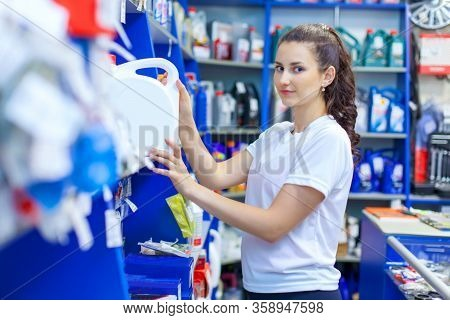A Young Girl Saleswoman Offers A Choice Of Engine Oil For The Engine In An Auto Parts Store