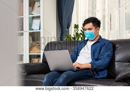 Attractive Asian Young Man Working Working With Laptop On Couch, Work From Home Ideas.