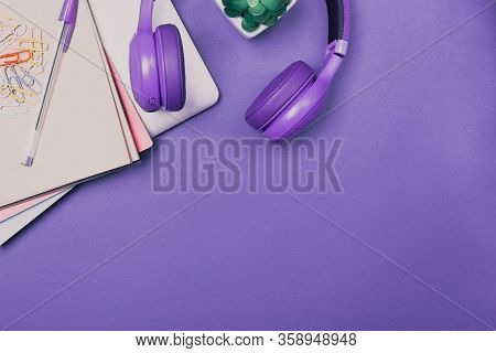 Top View Of Bright Colourful Desk Top. Laptop, Notebook, Ear Phones. Work Home Office. Creativity. C