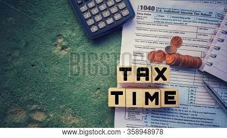Tax-filling Concept - Tax Time Words On Wooden Blocks With The U.s Irs 1040 Form,pen,calculator,note