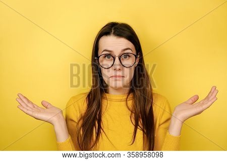 Clueless Uncertain Young Woman Wears Spectacles, Sweater, Spreads Hands, Being Doubtful, Looks At Ca
