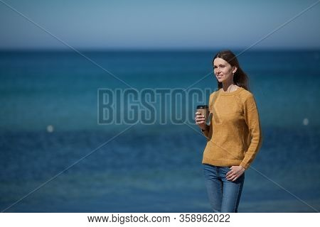 Beautiful Cute Girl In A Yellow Sweater On The Beach By The Sea And Drinking Coffee To Take Away . T