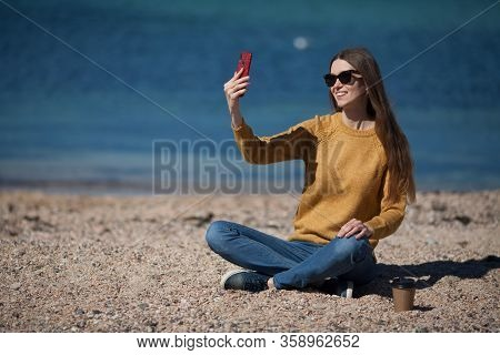 An Attractive Girl In A Yellow Sweater On The Beach By The Sea Takes A Selfie On Her Smartphone. The
