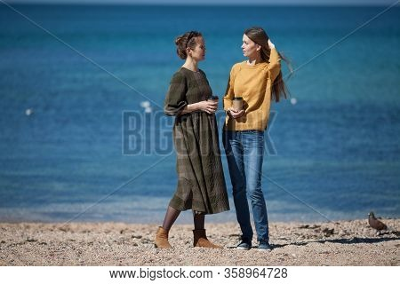 Two Beautiful Girl Friends Talk Emotionally On A Walk On The Beach By The Sea. The Concept Of Live C