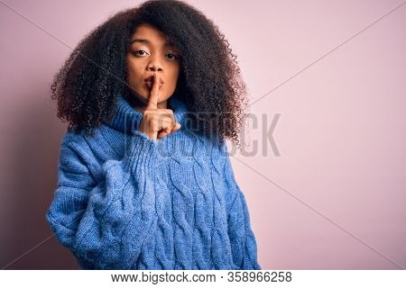 Young beautiful african american woman with afro hair wearing winter sweater over pink background asking to be quiet with finger on lips. Silence and secret concept.