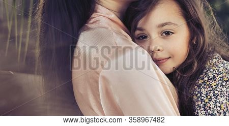Young mom hugging her preatty daughter