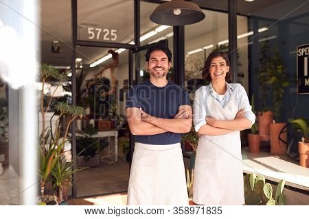 Portrait Of Smiling Male And Female Owners Of Florists Standing In Doorway Surrounded By Plants