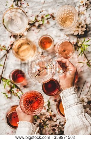 Womans Hands Over Rose Wine Over White Marble Background
