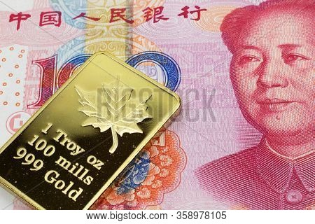 A Macro Image Of A Red Chinese One Hundred Yuan Bank Note With A Gold Bar.  Shot Close Up.