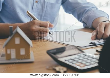 Young Man Is Signing Financial Mortgage Contract Of Sale For A New House With Real Estate Agent At O