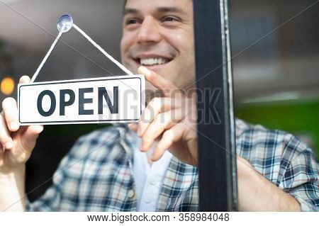 Smiling Small Business Owner Turning Around Open Sign On Shop Or Store Window Or Door