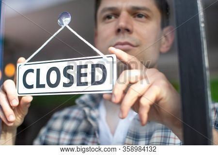 Small Business Owner With Serious Expression Putting Up Closed Sign During Recession Or Health Pande