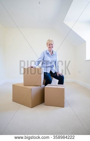 Portrait Of Senior Woman Downsizing In Retirement Sitting On Boxes In New Home On Moving Day