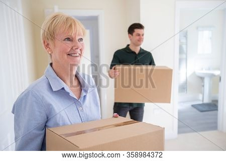 Senior Woman Downsizing In Retirement Carrying Boxes Into New Home On Moving Day With Removal Man He