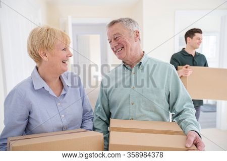 Senior Couple Downsizing In Retirement Carrying Boxes Into New Home On Moving Day With Removal Man H