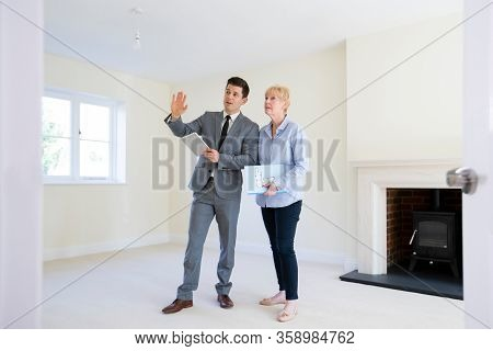 Realtor With Digital Tablet Showing Senior Woman Looking To Downsize Around Retirement Home