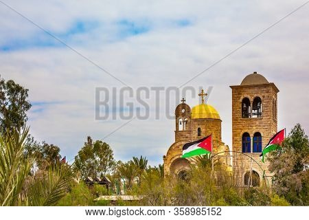 Qasr el-Yahud is the site of the baptism of Jesus Christ by John the Baptist on the West Bank. Church of John the Baptist. Jordanian national flags fluttering on Jordanian side. e
