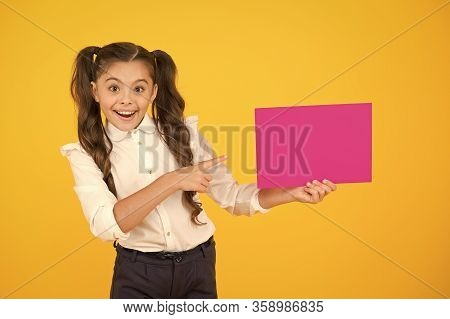 Presenting Your Product. Happy Little Girl Pointing Finger At Blank Pink Paper For Product Advertisi