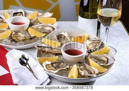Fresh Oysters In A White Plate With Ice And Lemon. Open Oysters And Glass Of White Wine. Tasty Oyste
