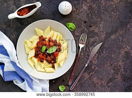Penne Pasta With Tomato Sauce, Carrots And Black Beans In A Gray Bowl On A Dark Concrete Background.