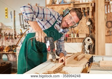 Man as a joiner in the apprenticeship works with the hand drill in the workshop