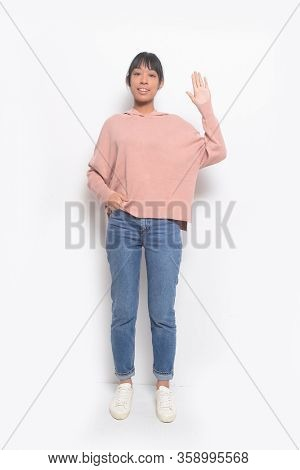 Full length young woman in brown sweater with blue jeans isolated doing stop sing with palm of the hand.