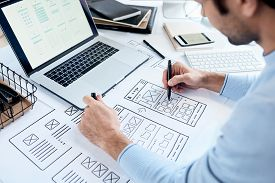 Close-up of busy designer sitting at table with laptop and drawing icons placement for ui design