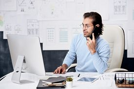 Content brown-haired manager of IT company sitting at desk and talking to colleague by phone while analyzing data on computer