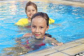 Happy Little Girls Swimming And Smiling In Outdoor Pool At Sunset