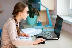 Beautiful Young School Girl Working At Home In Her Room With A Laptop And Class Notes Studying In A
