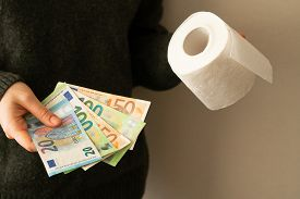 Girl Holds Euro Banknotes And Toilet Roll. Close-up